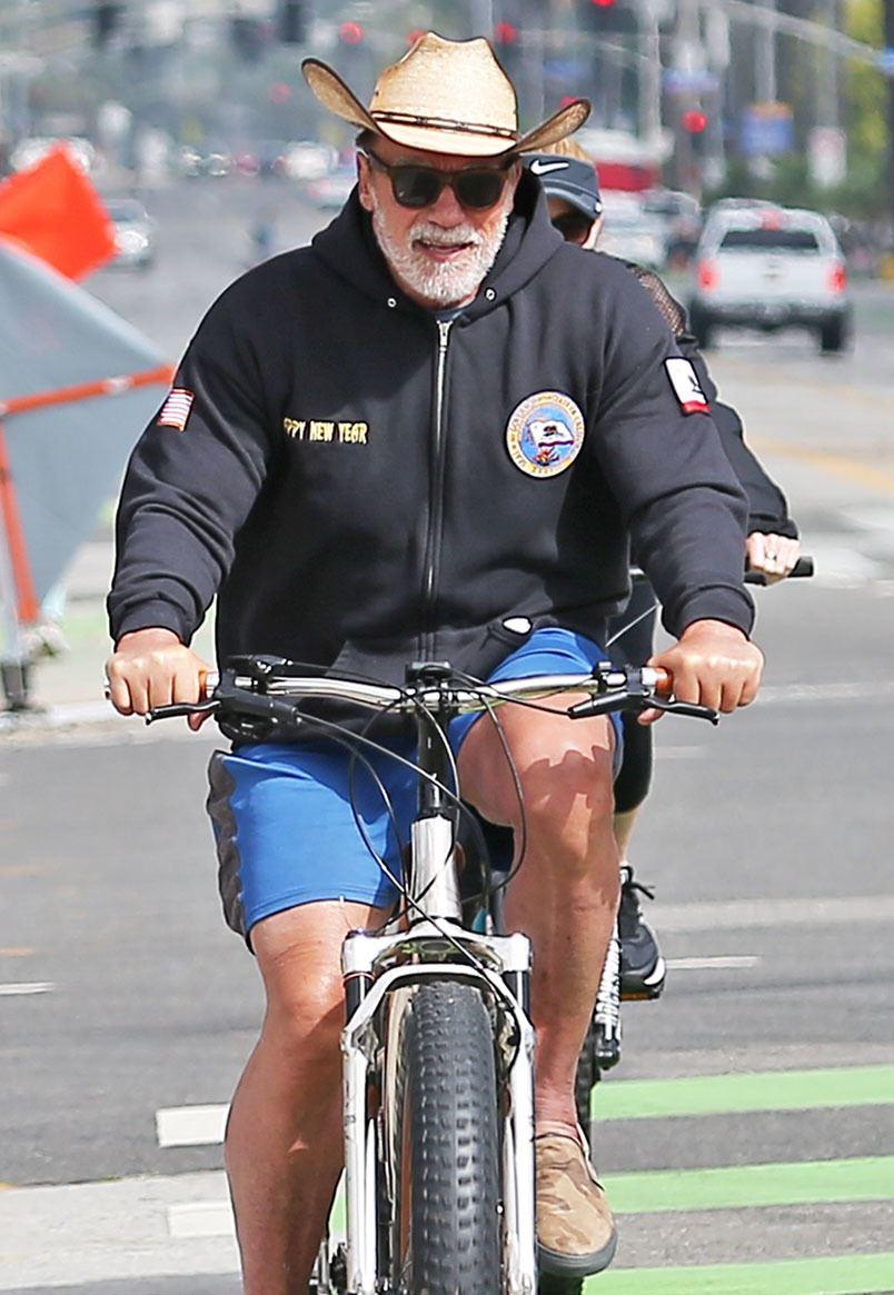 En mand med stråhat på cykel, der smiler