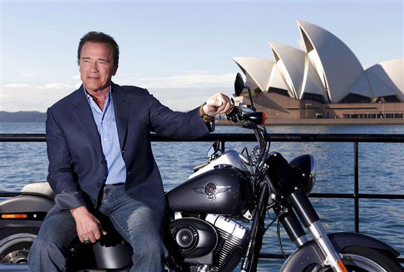 Arnold Schwarzenegger på motorcykel med Sydney Opera Hus i baggrunden.