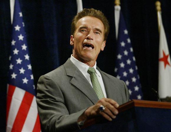 Arnold Schwarzenegger på talerstol med det amerikanske flag bag sig.