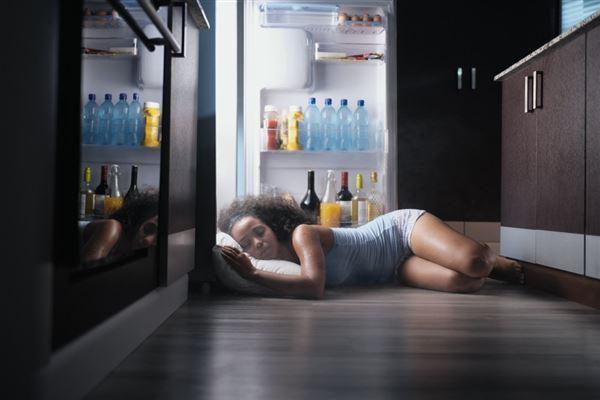 En pige ligger og sover op af et åbent køleskab