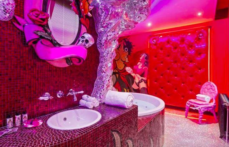 Meget lyserødt badeværelse med frække tegninger på væggen.