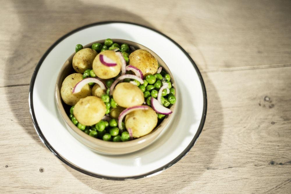 En skål med kogte kartofler og ærter.