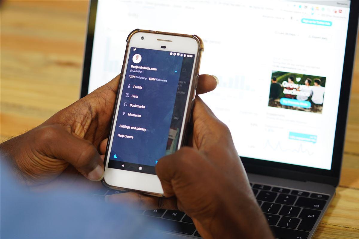 Mand med mobiltelefon foran pc-skærm