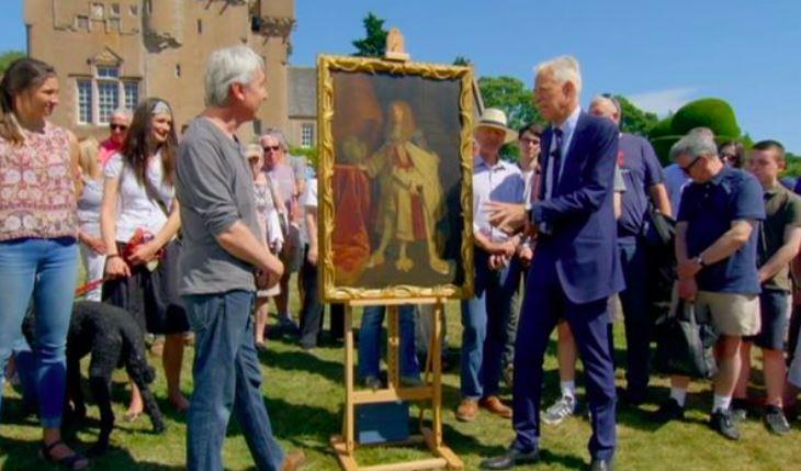 En mand kigger på en anden mand og et stort maleri mellem de to og et slot i baggrunden.