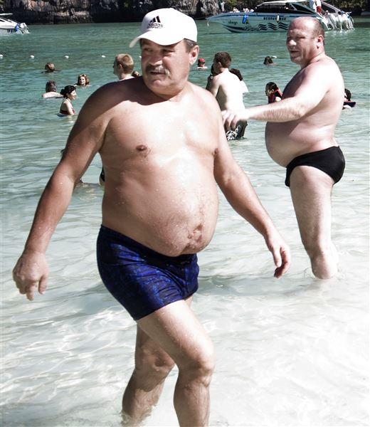 To mænd med ølmaver i små badebukser på en strand i Thailand.