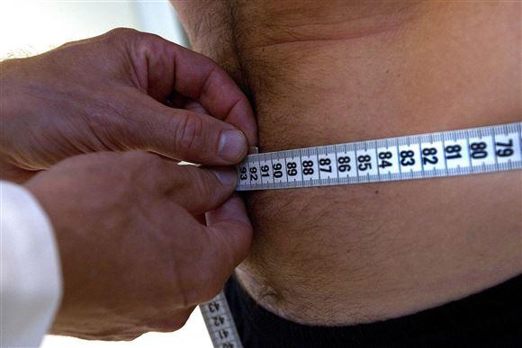 Mand får målt sin mave med et centimeterbånd