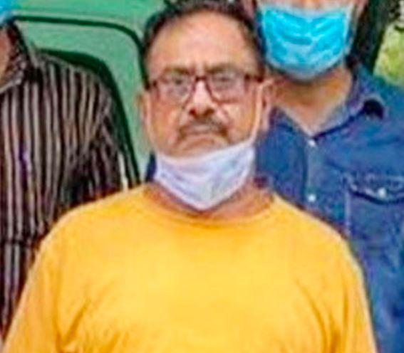 En mand i gul t-shirt og beskyttelsesmaske om halsen føres ud af politiet