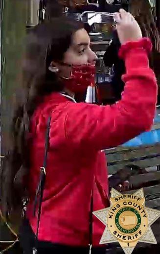 En teenager i en rød jakke med mundbind