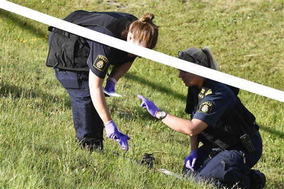 To politbetjente afsøger noget græs