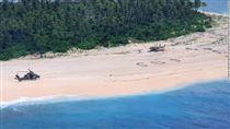 Helikopter på strand med SOS skrevet i sandet