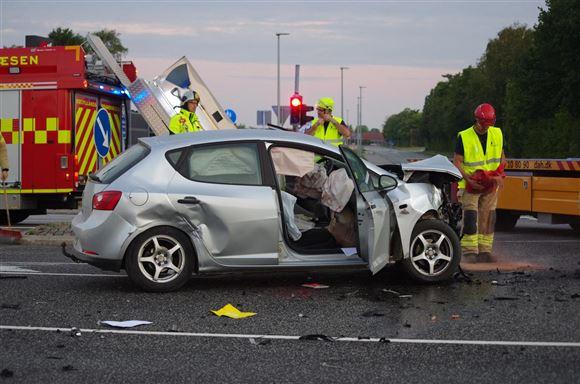 En smadret søvgrå bil med redningsfolk omkring.