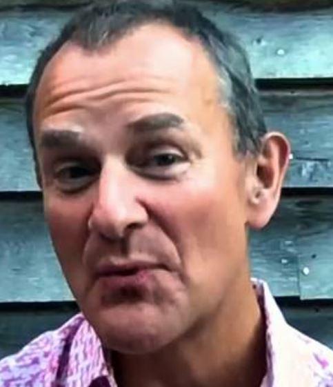 Hugh Bonneville fra Downton Abbey i en åbentstående pink skjorte