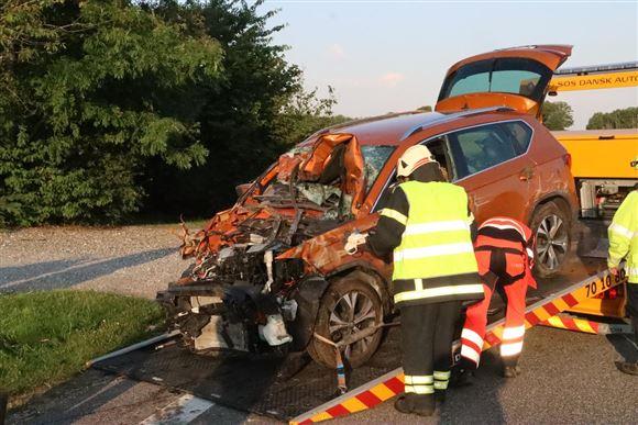 En smadret bil bugseres op på et fejeblad