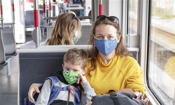 Mor og søn med mundbind i bus