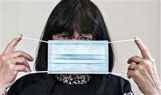 Kvinde holder mundbind foran ansigtet