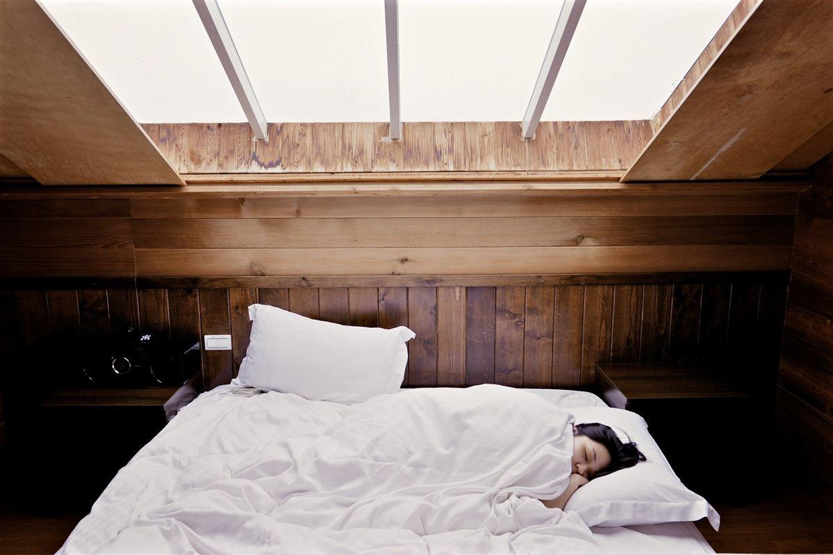 En sovende kvinde i en kæmpe seng med et ovenlysvindue over sig