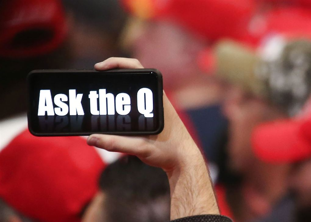 To personer holder deres mobiltelefoner op og viser deres støtte til konspirationsteorien QAnon