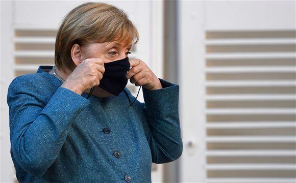 Angela Merkel i blå kjole med et sort mundbind.