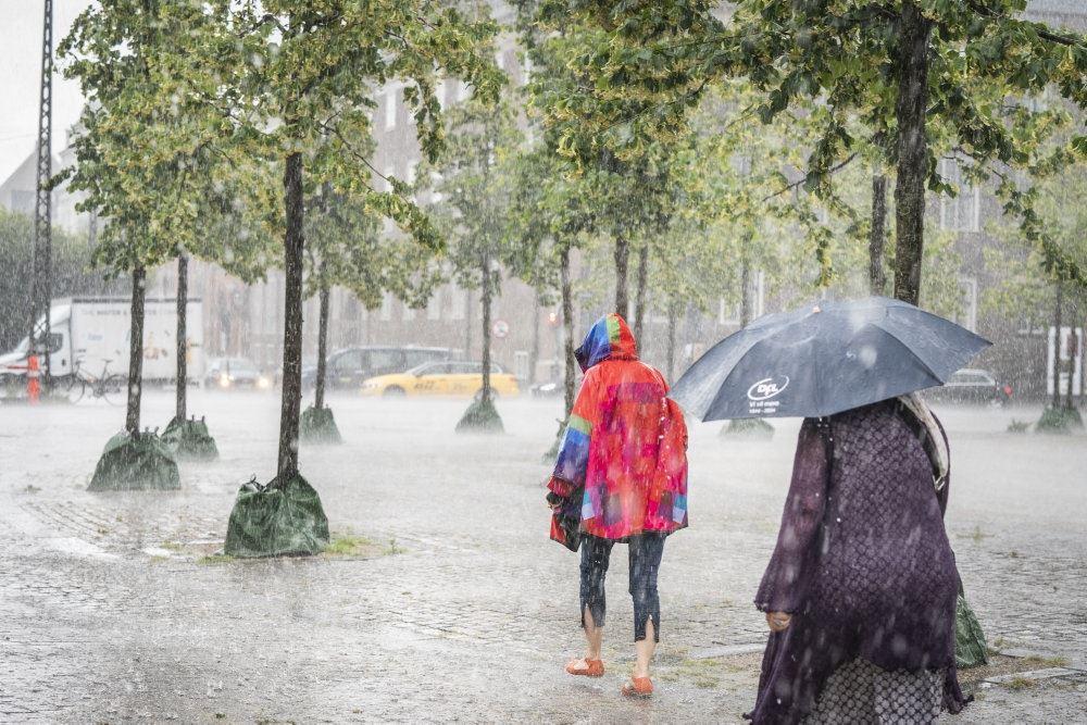 Folk i regntøj igår på gaden i voldsomt regnvejr