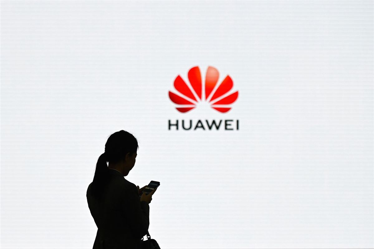 En silhouet af en kvinde med en mobiltelefon foran et stort Huawei-reklame