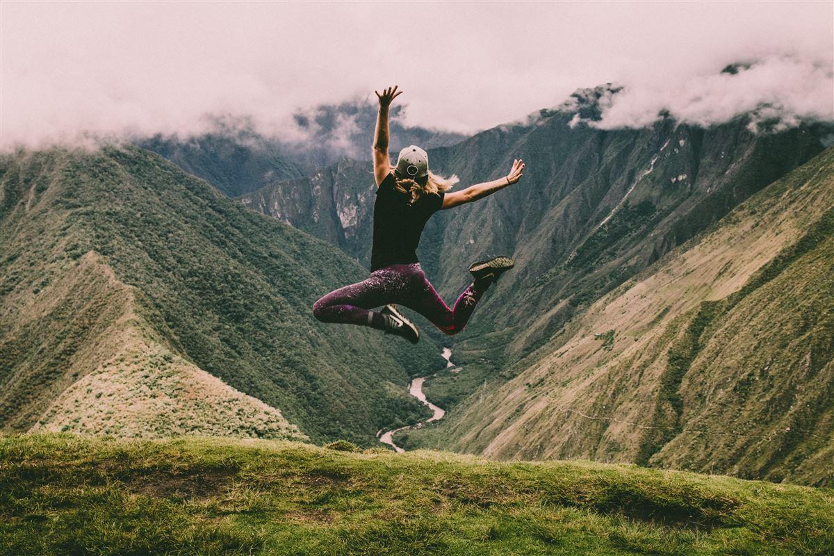 En pige hopper op i luften i træningstøj - forgrunden er et bjergpas