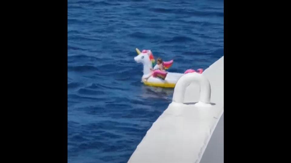 En lille pige på et badedyr er drevet til havs og nærmes af en færge