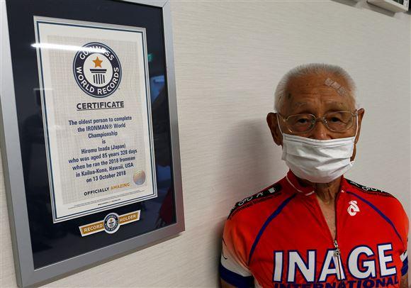 den 87-årige japanske triatlet Hiromo Inada ses foran sit diplom fra Guinness World Records som beviser at han er den ældste til at gennemføre en ironman i triatlon