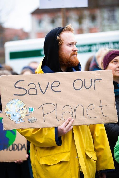 Mand med et skilt, hvor der står Save our planet