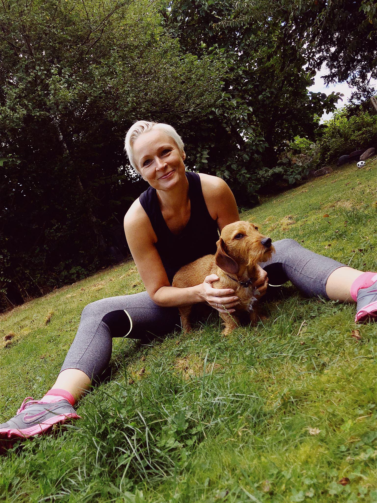 Skuespilleren Vicki Berlin i træningstøj med en lille brun hund