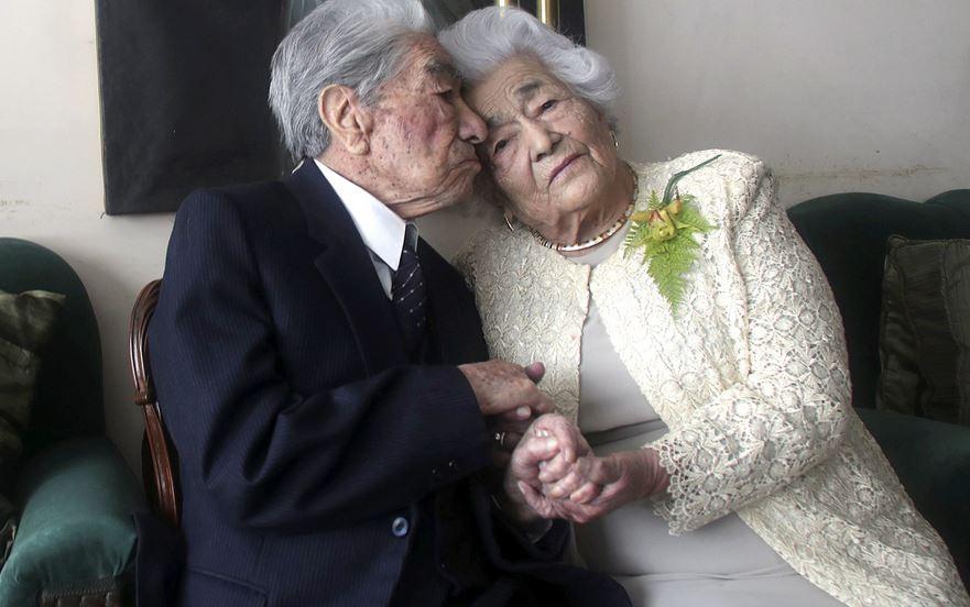 Et gammelt ægtepar i pænt tøj på en sofa giver heninden et kys