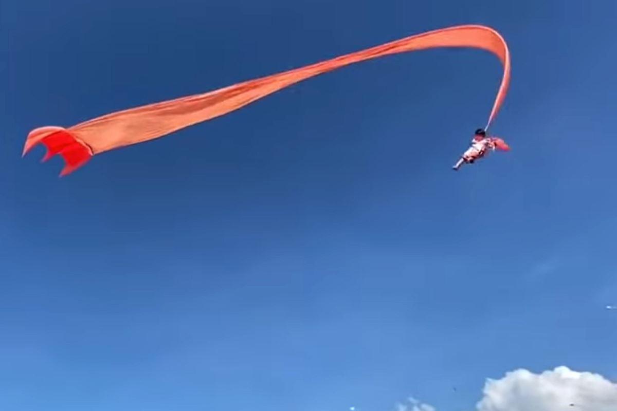 En lille pige hænger i en lang orange drage cirka 30 meter over jorden