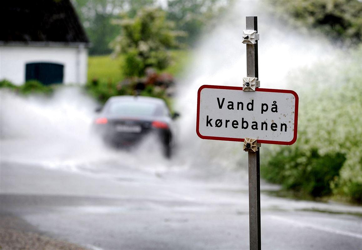 En bil kører igennem en kæmpe vandpyt