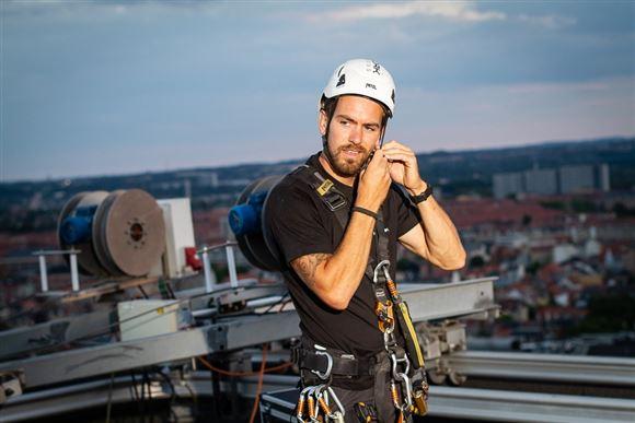 En mand med hjelm og reb og liner på toppen af et højhus.