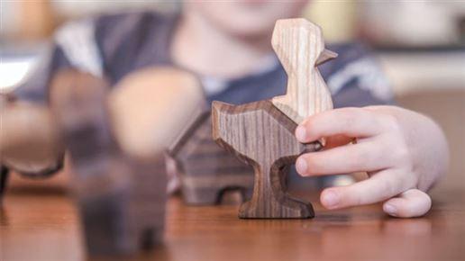 Et barn leger med nogle træfigurer