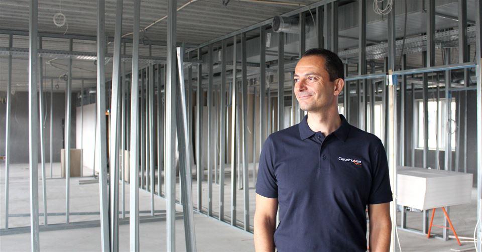 En mand i blå poloshirt står på en etage fyldt med rør fra gulv til loft