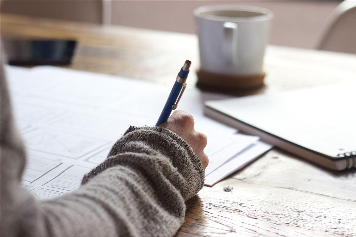 en studerende sidder med en kop kaffe og skriver