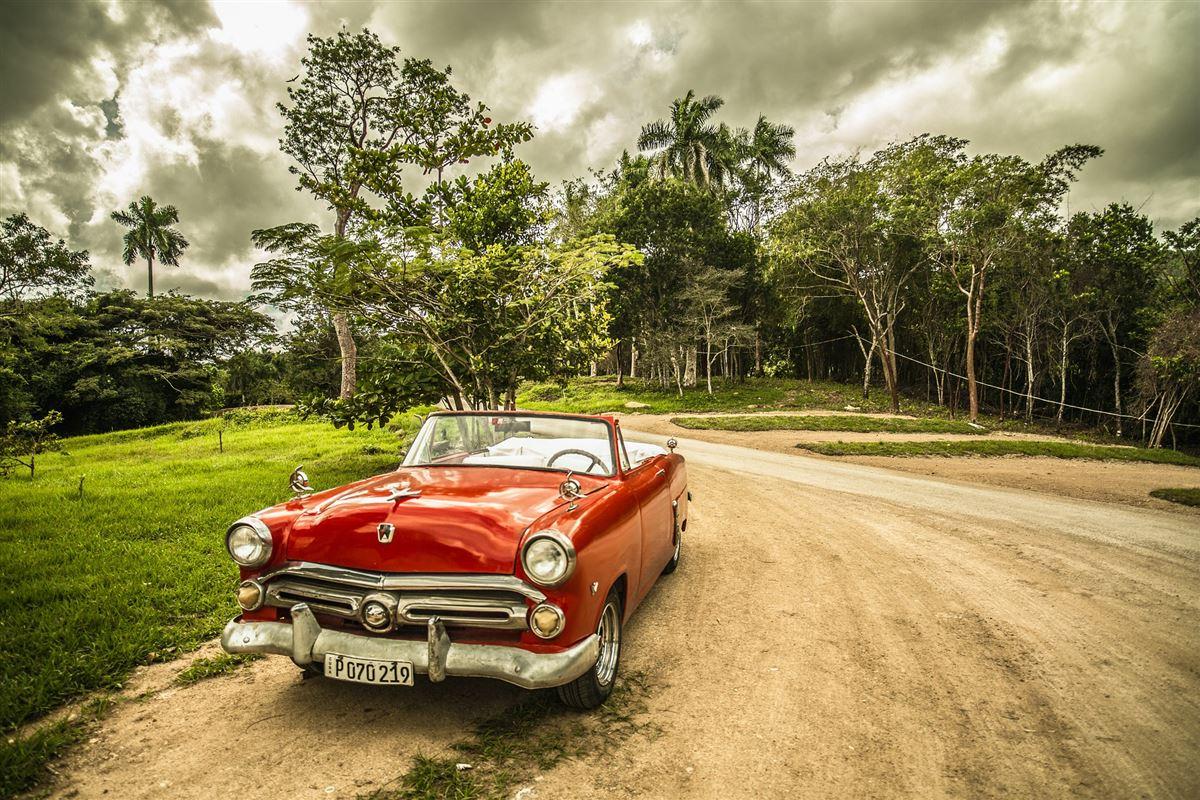 En gammel åben rød amerikanerbil uden for en jungle på Cuba