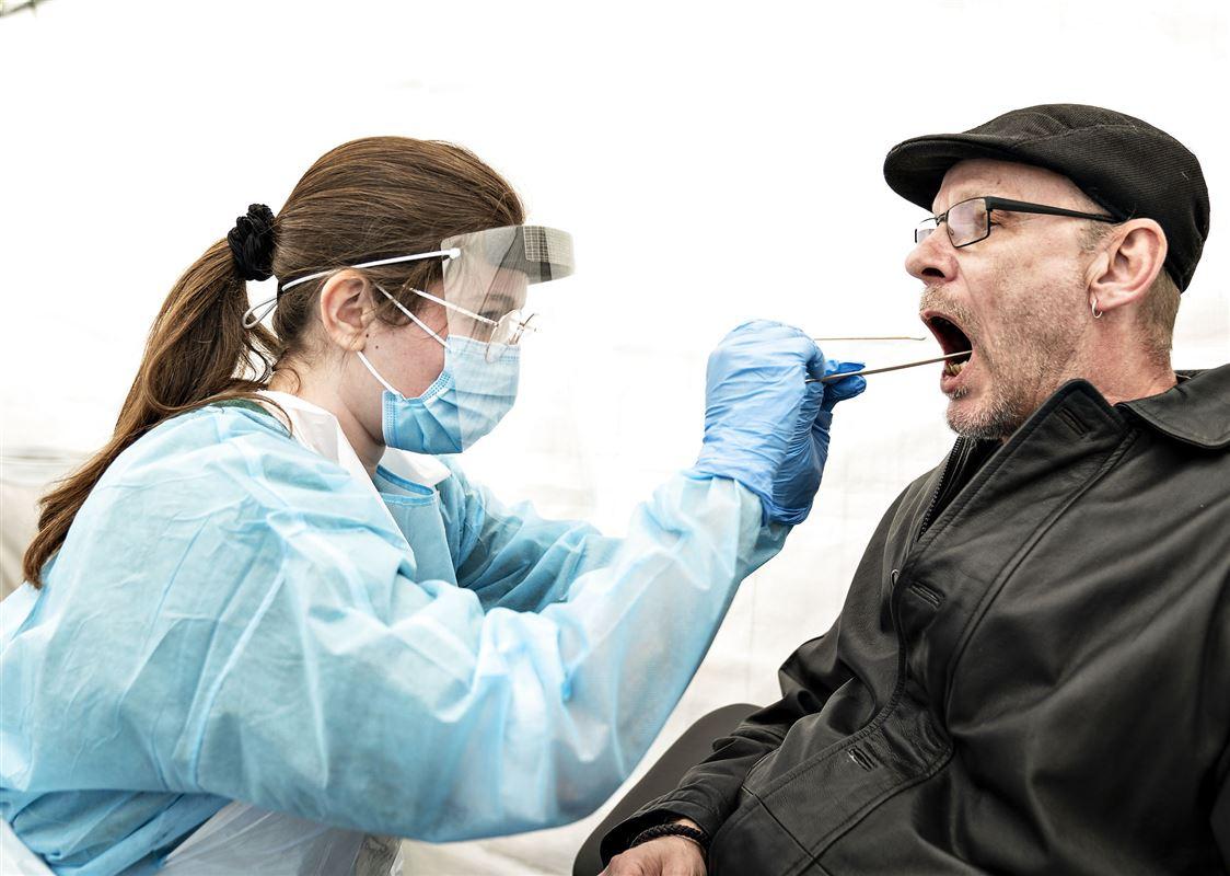 En sundhedsarbejder foretager en coronatest på mand med kasket