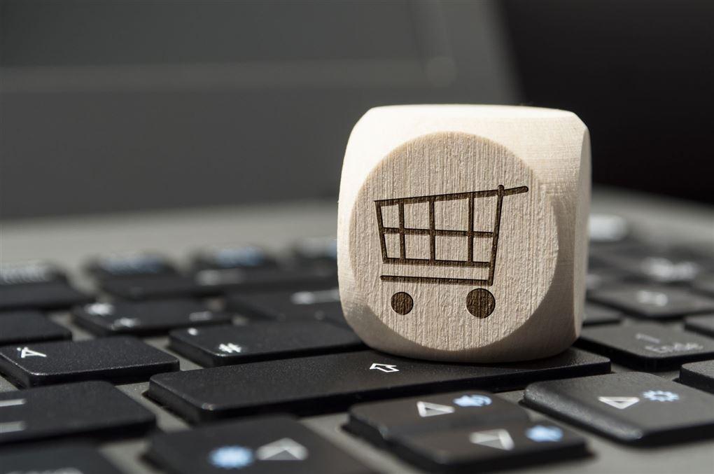 Billede af en terning med en indkøbsvogn på en åben laptop