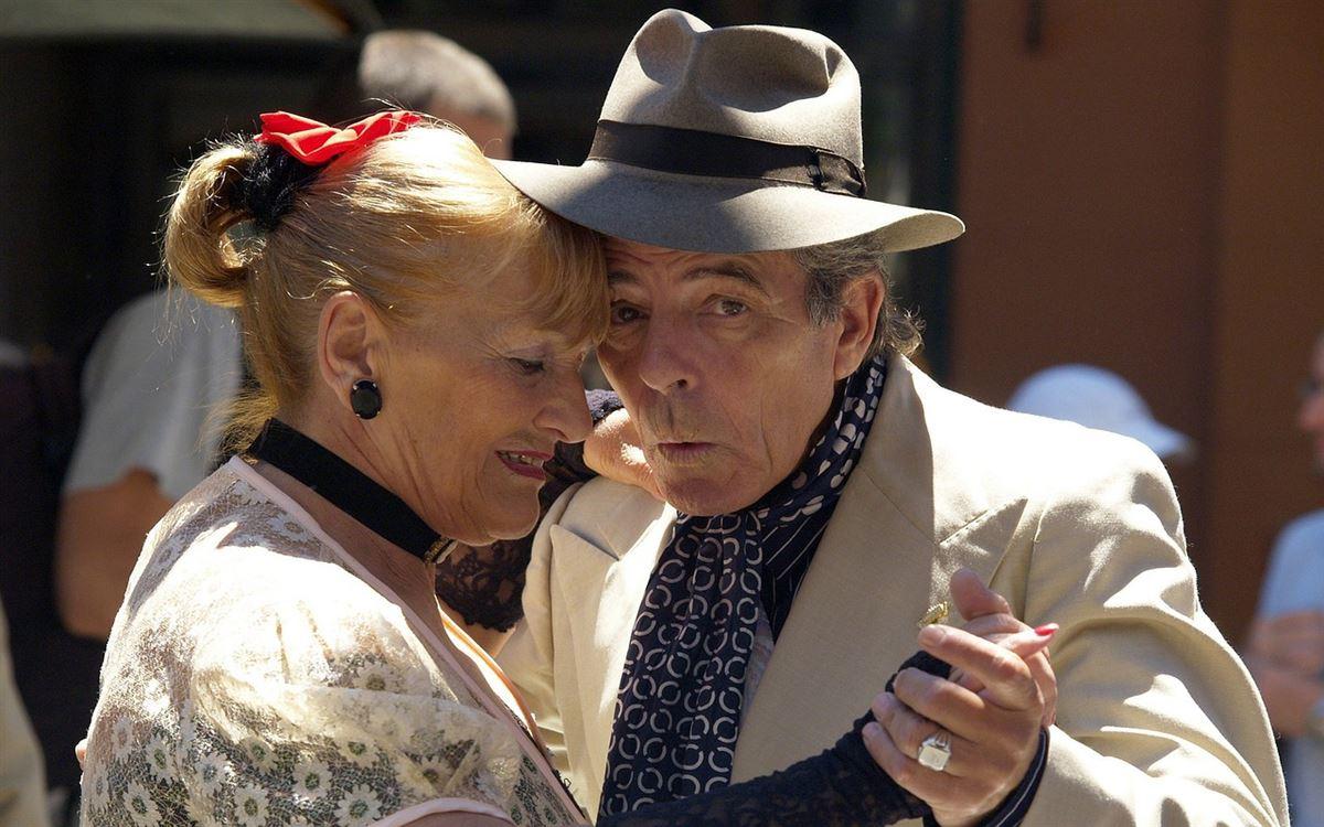 Et ældre par danser i solen - han har hat på og hun en rød sløjfe i håret