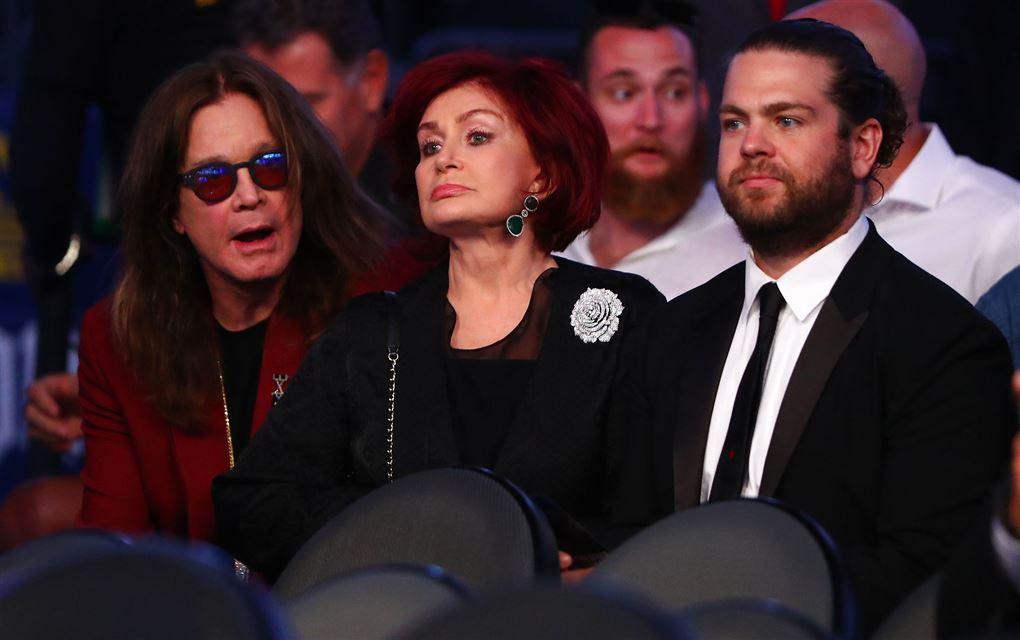 Ozzy Osbourne sidder med solbriller på ved siden af sin kone Sharon, som ser sur ud. Parrets søn Jack Osbourne er også med på billedet. Han sidder ved siden af sin mor med et sort jakkesæt og en hvid skjorte på.