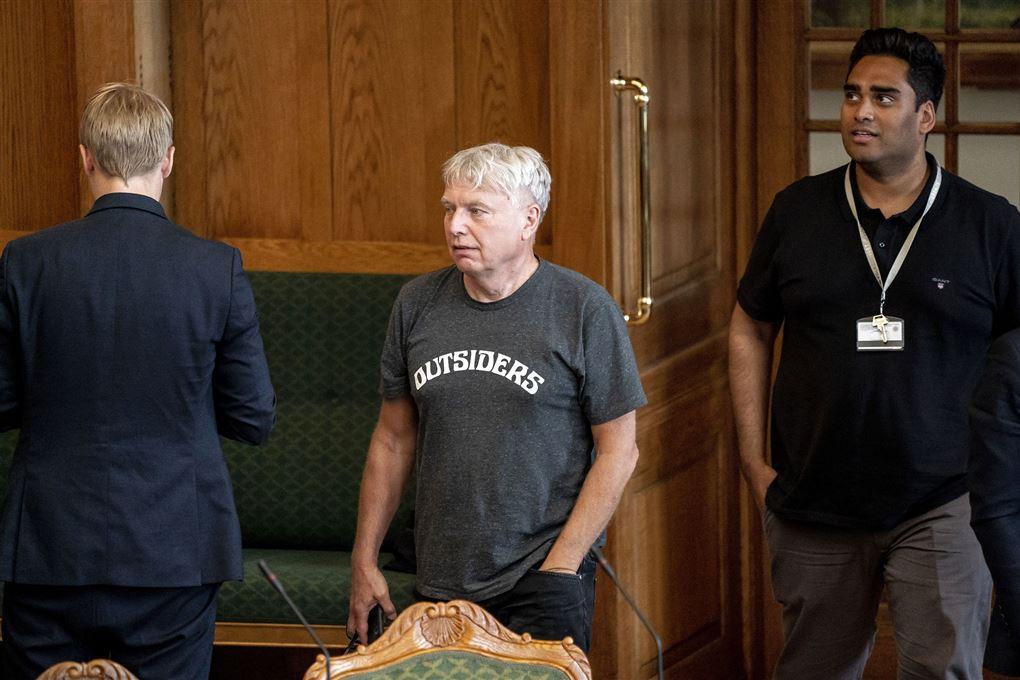 Politiker Uffe Elbæk i Folketingssalen iført mørkegrå t-shirt med hvide bogstaver, hvor der står Outsiders på maven. Bag ham ses Sikandar Siddique der er iført en sort t-shirt.