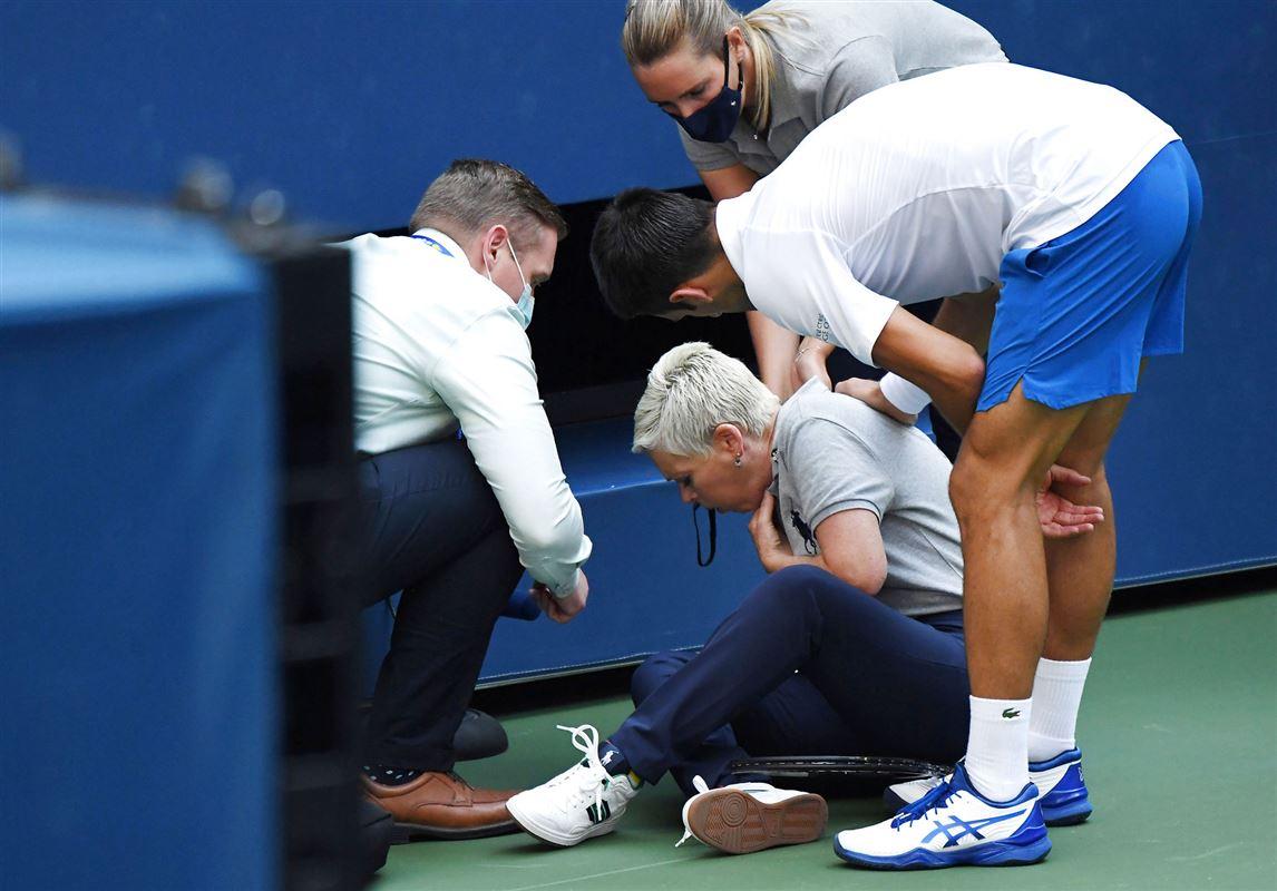 Tennisspilleren Novak Djokovic står ved en linjedommer som han har ramt på halsen