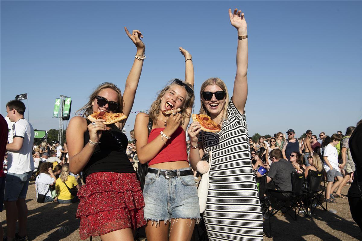 Tre koncertgæster til Grøn Koncert spiser pizza