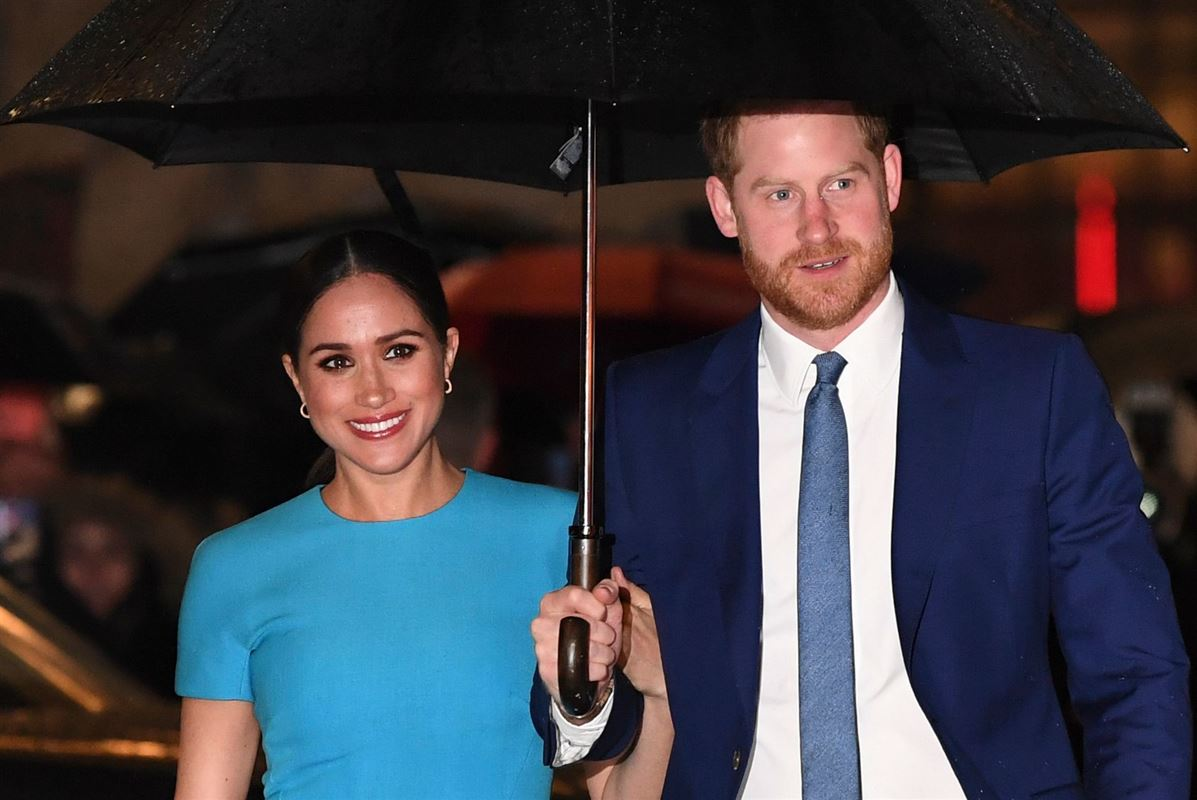 Meghan i en blå kjole og Harry i jakkesæt, som holder en paraply