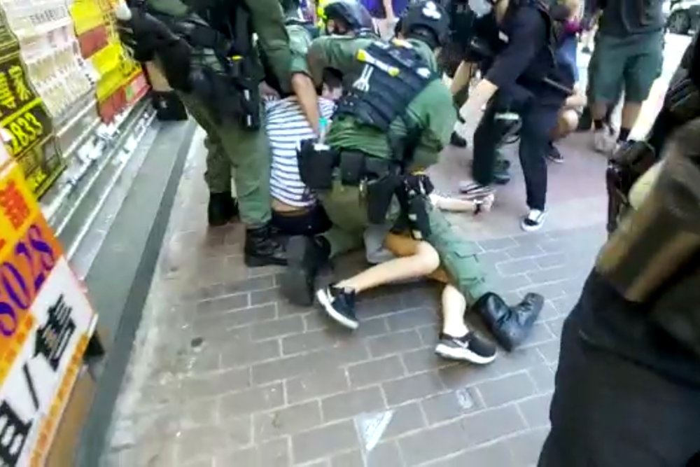 Et par små bare ben ses under en bevæbnet politibetjent. Pigen ligger på et fortov.