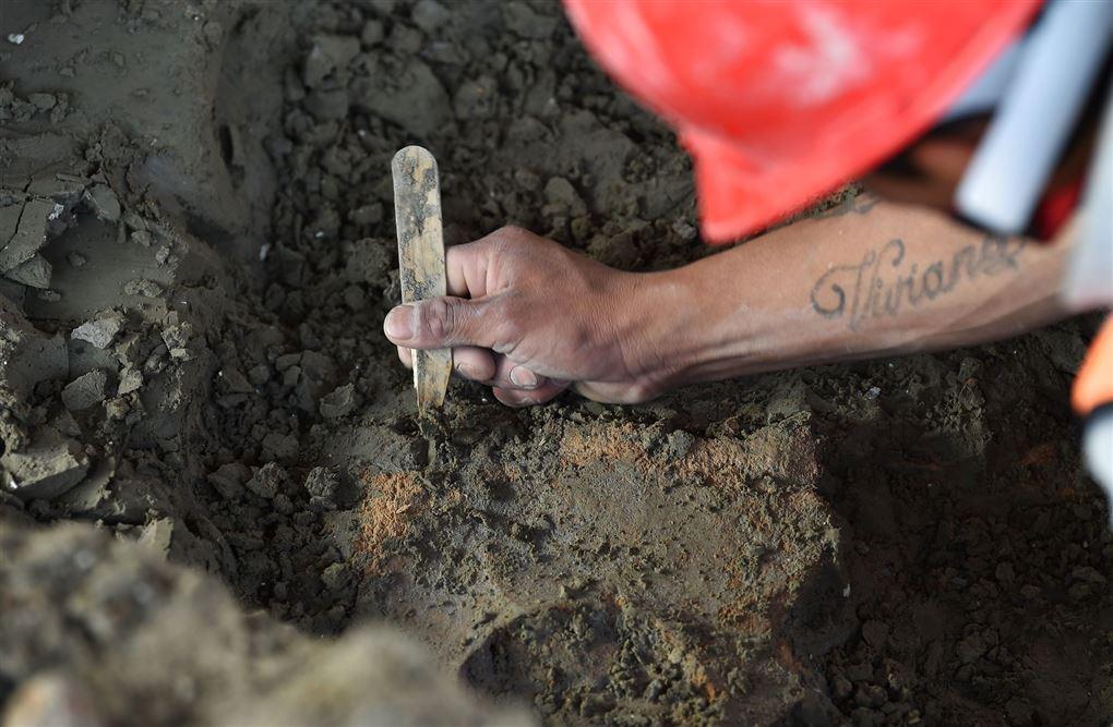 nærbillede af en arkæolog der arbejder i udgravningen