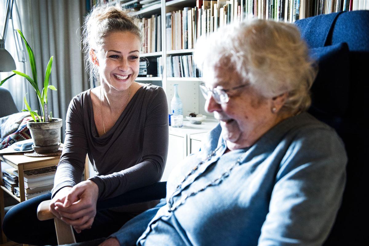 En smilende kvinde sidder inde i stuen hos en ældre dame