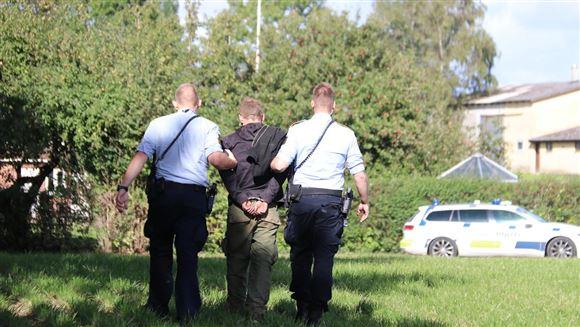 To betjente går med en mand i håndjern mellem sig