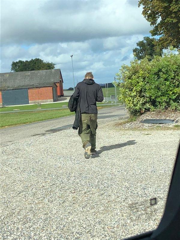 En mand i grønne armybukser og mørk hættetrøje bagfra